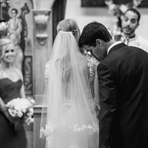 groom kisses bride on the shoulder during ceremony