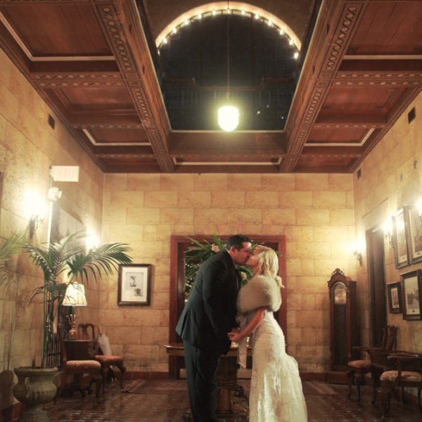 Bride and Groom Kiss in Foyer of The Treasury on The Plaza