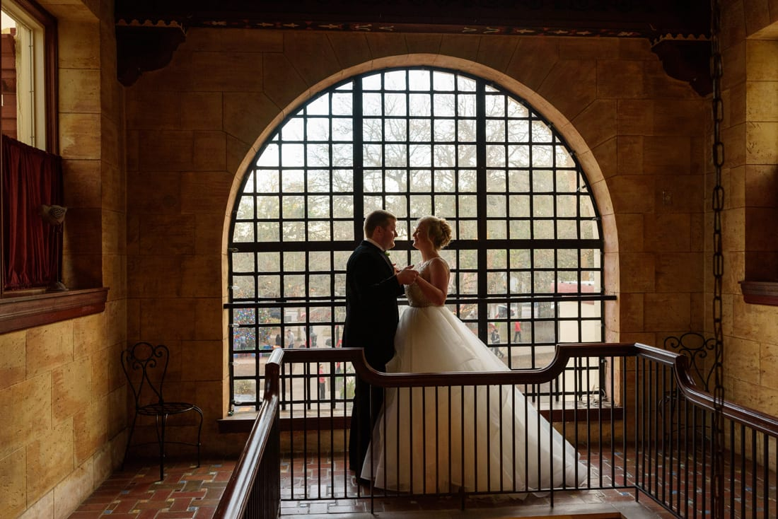 Bride and groom first look in front of beautiful window at The Treasury on the Plaza