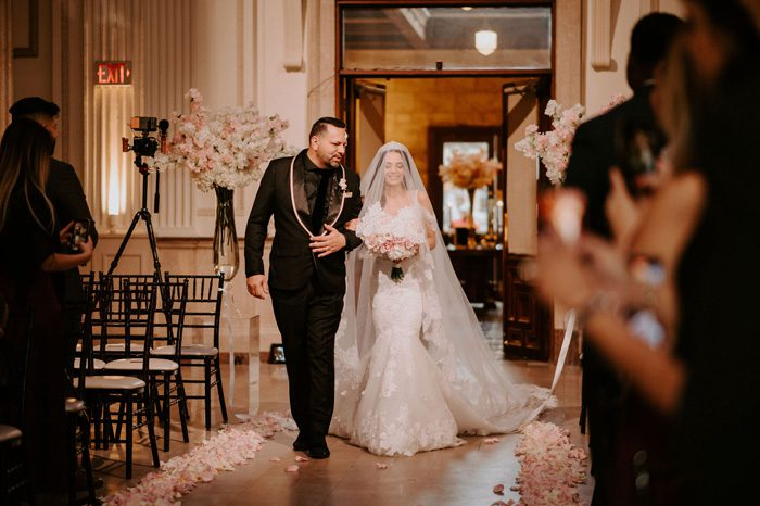 father and bride walk down the aisle | Glam Wedding with a Rock and Roll Surprise at The Treasury | Cristal + Steven